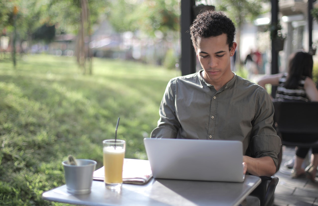 focused-black-male-freelancer-using-laptop-in-street-cafe-3799115
